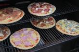 Con Weber's Pellet Grill Smokefire, hai tutto lo spazio per cuocere più pizze contemporaneamente.  Se prerisci prima la base della pietra per pizza, puoi eventualmente spostarla sul piatto.  Foto: Gladcon / Weber